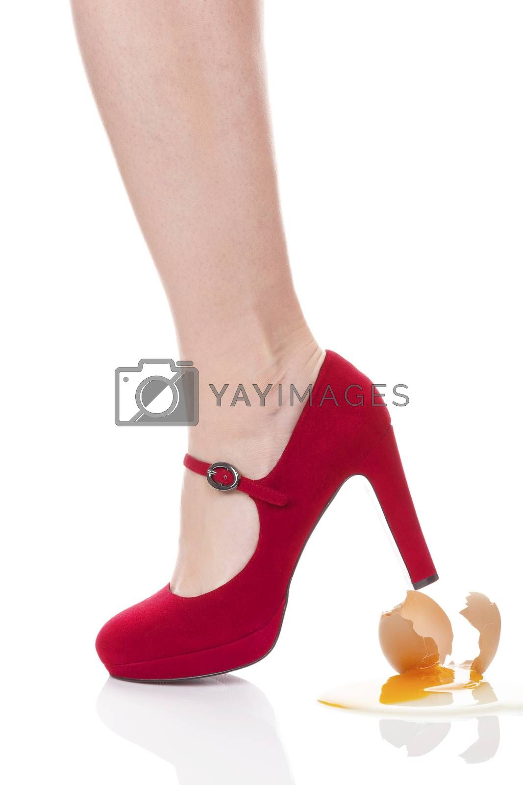 Domestic violence against men. Female leg in high heels breaking a egg isolated on white background.