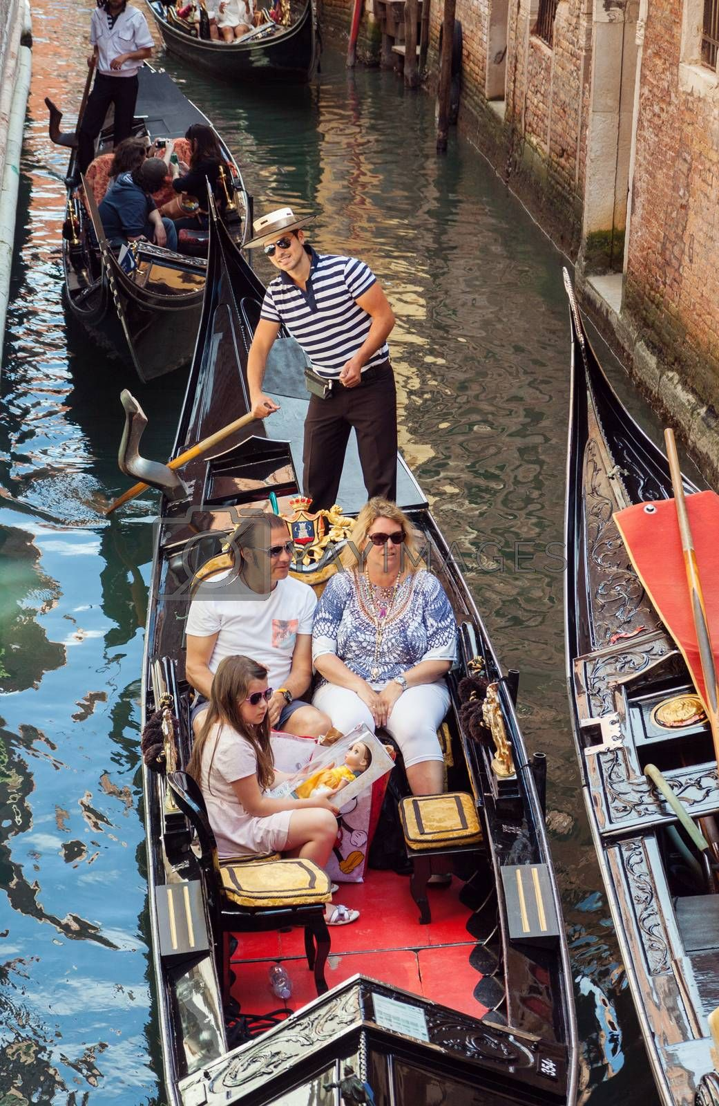VENICE, ITALY - MAY 27, 2015: Parents and young girl sailing in gondola, in Venice, Italy. Gondolier is smiling at camera.