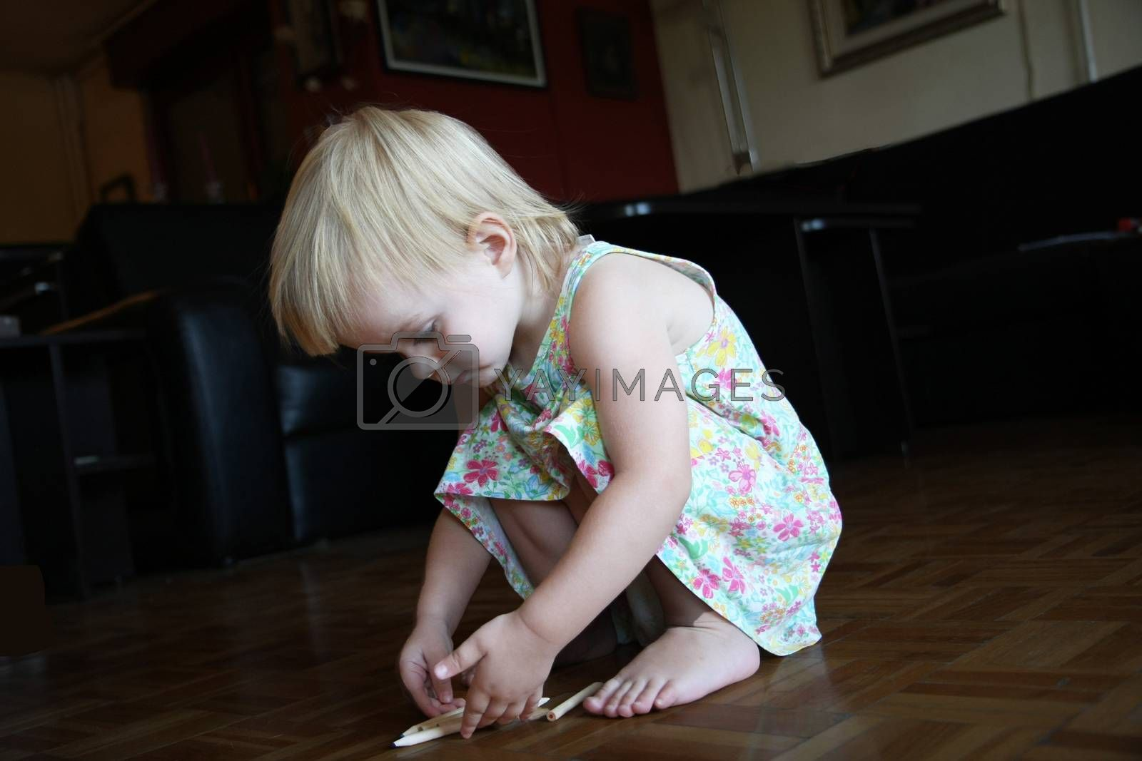 Cute young girl playing with pens on the floor
