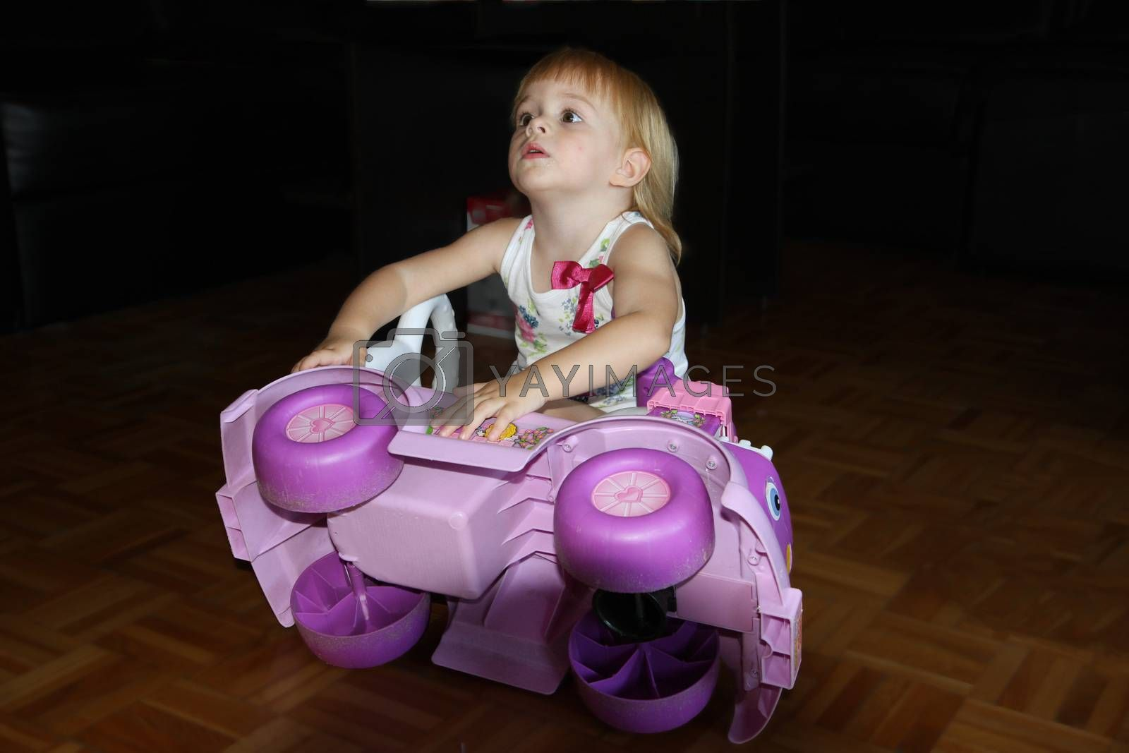 Cute young girl playing with plastic car on the floor