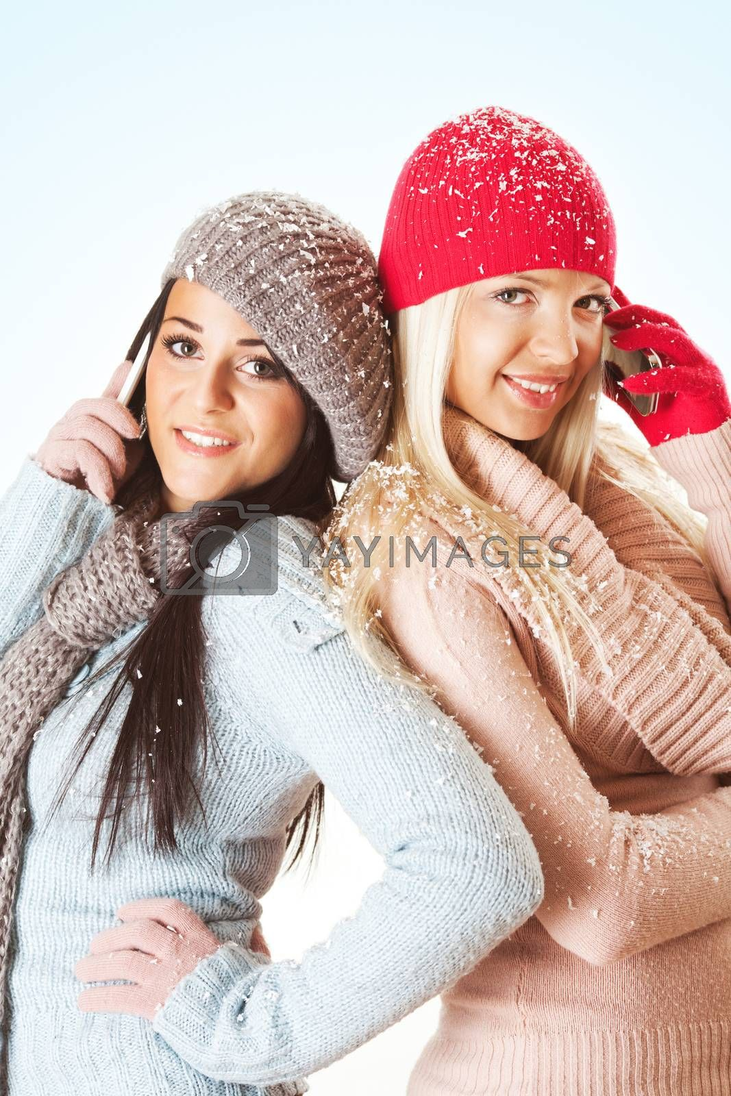 Beautiful girls with mobile phone on winter day