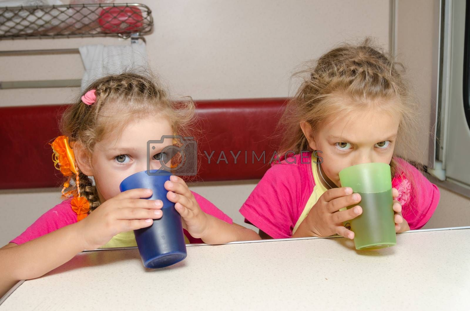 Two children drink tea in train at the table on the lower place in the second-class compartment wagon by Madhourse