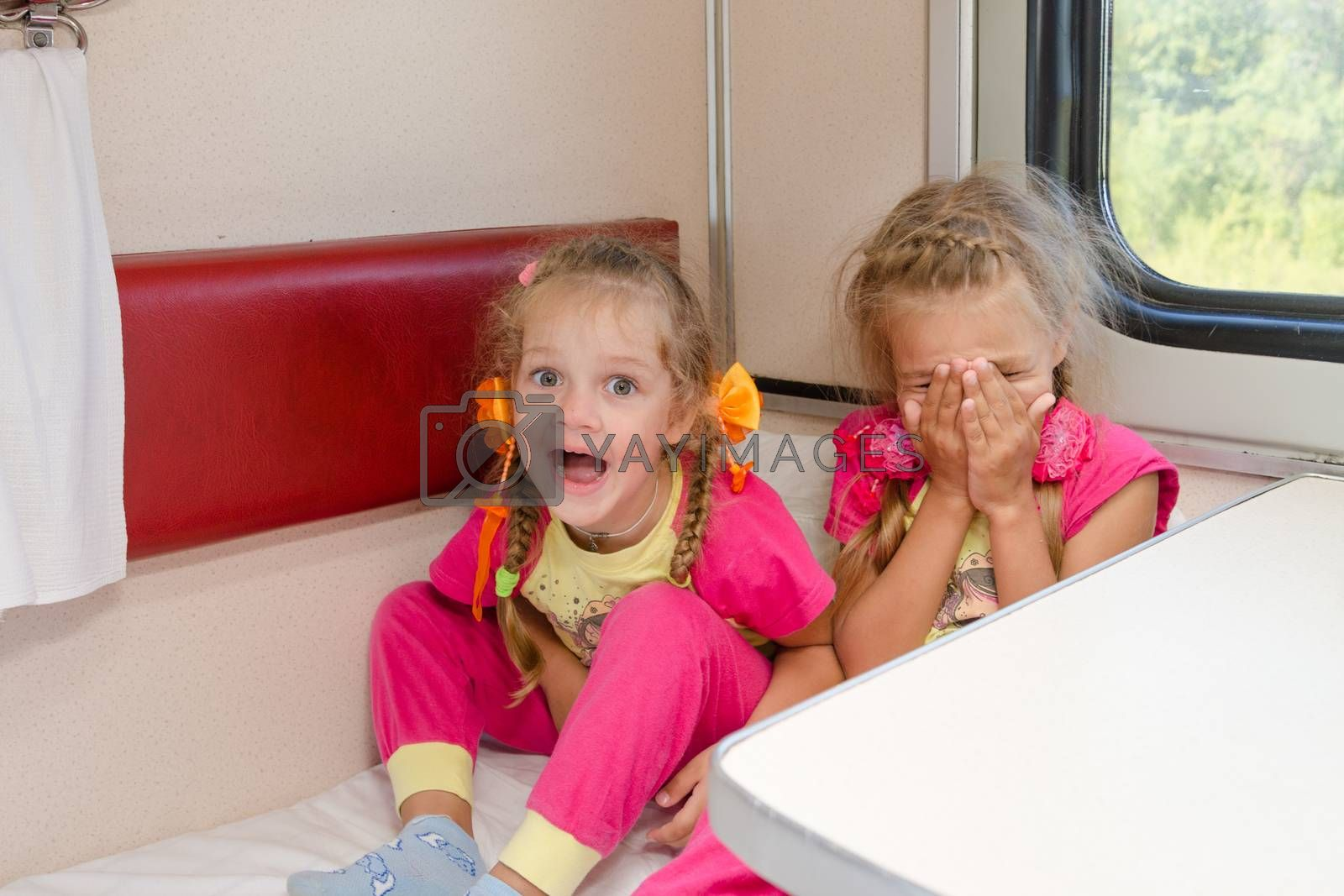 Two cheerful little girls are sitting on the train on the lower second-class place car in the same pajamas