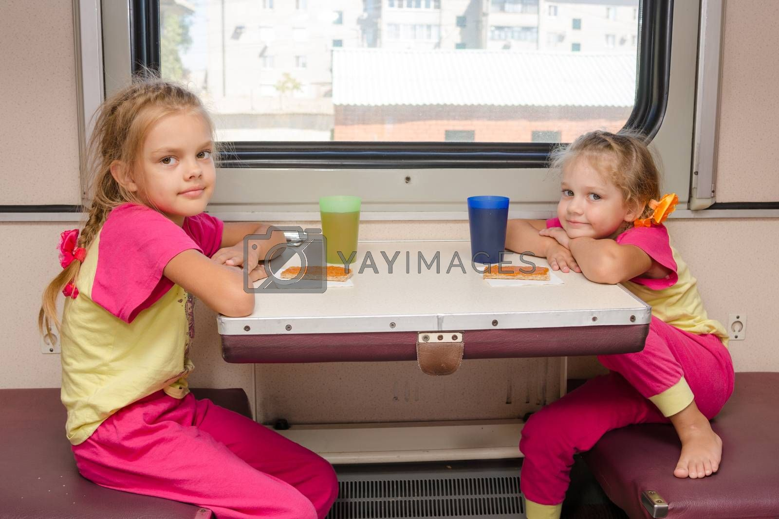 Two little girls on the train sitting at the table in the outboard second-class car in the same clothes