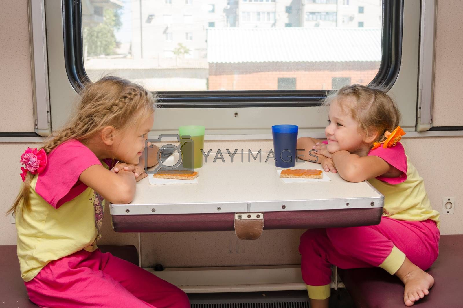 Two little girls with a happy face looking at each other on the train sitting at the table on outboard second-class carriage by Madhourse