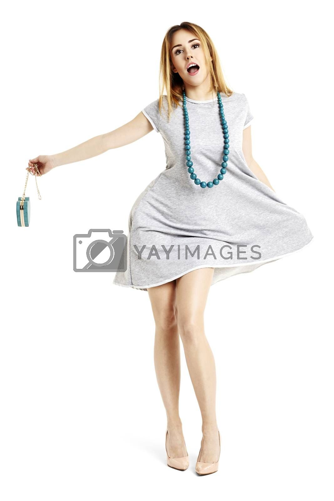Full length portrait of attractive woman singing. She looks into space and holding a handbag.