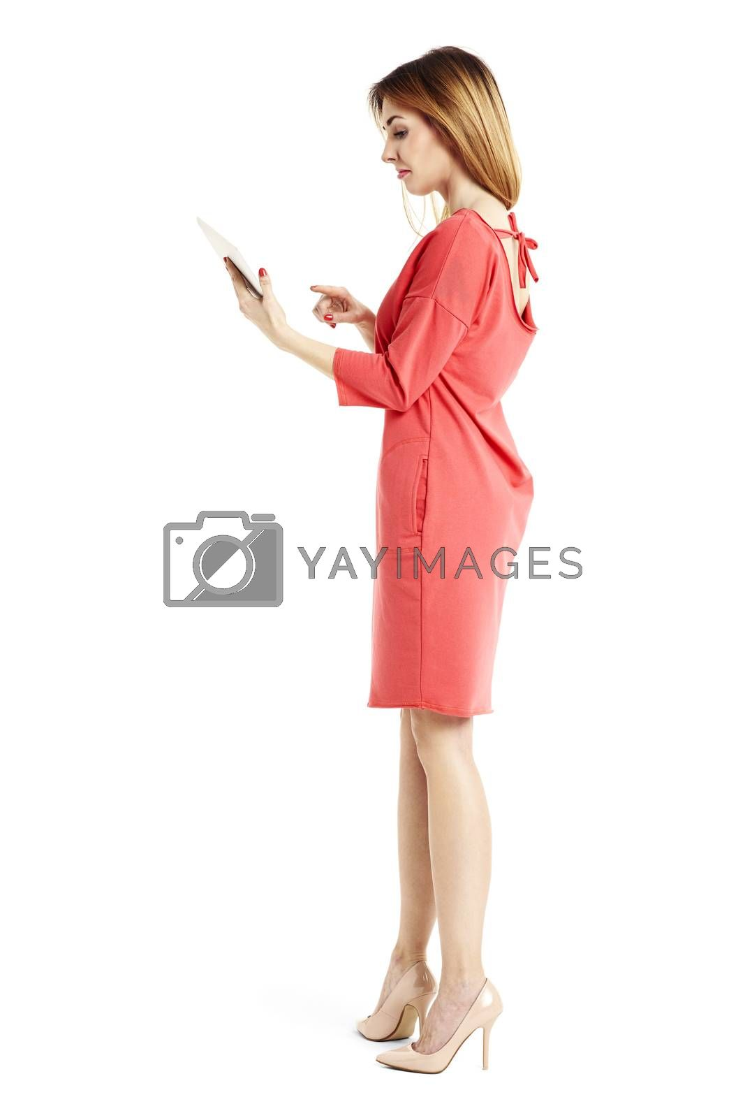 Studio shot of young attractive woman is reading from digital tablet.
