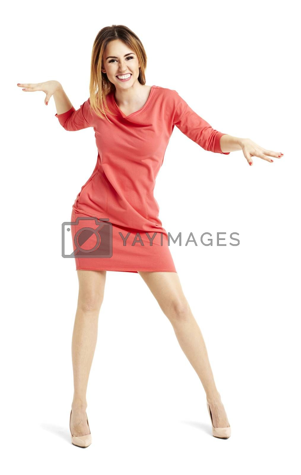 Full length portrait of pretty woman in a red dress. She is dancing.