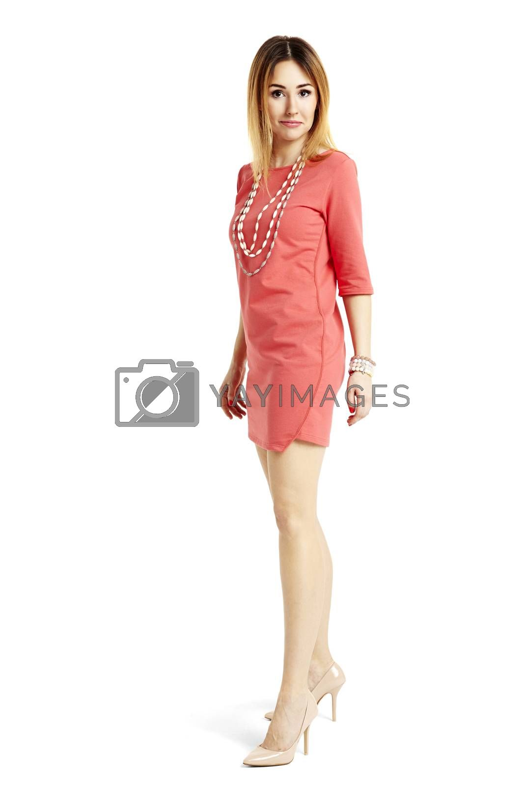 Studio shot of beautiful woman in red dress standing against white background.