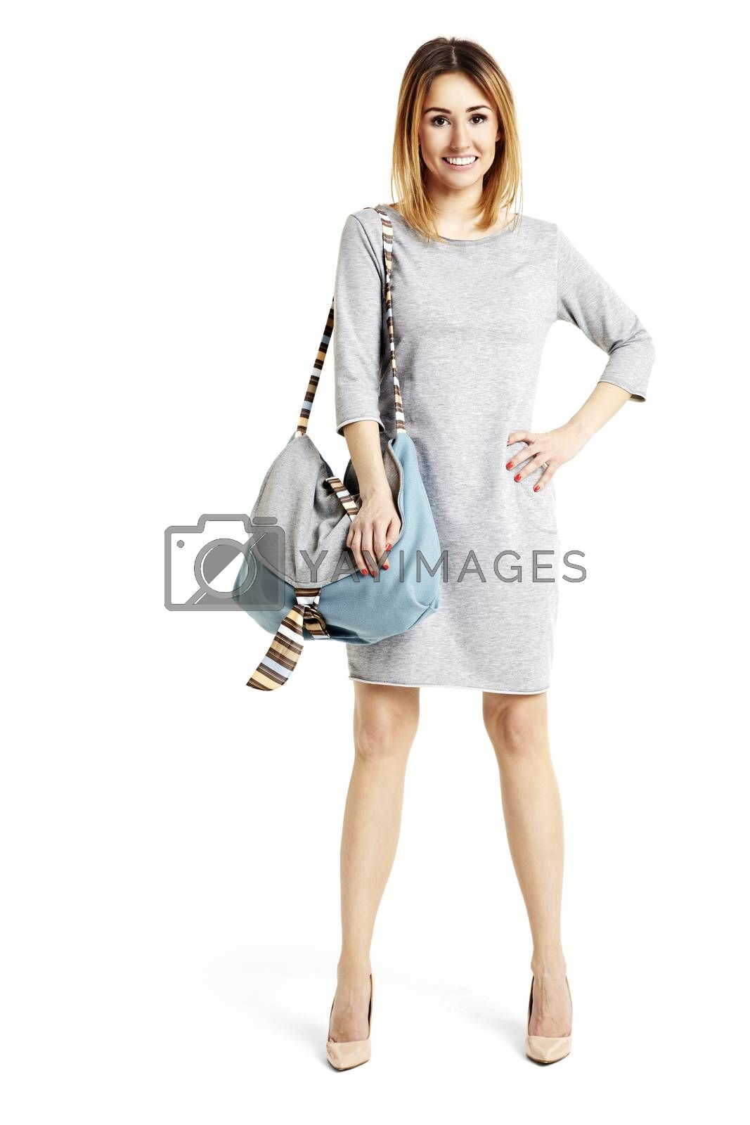 Studio shot of young woman with a bag. She hold a hand on her hip.