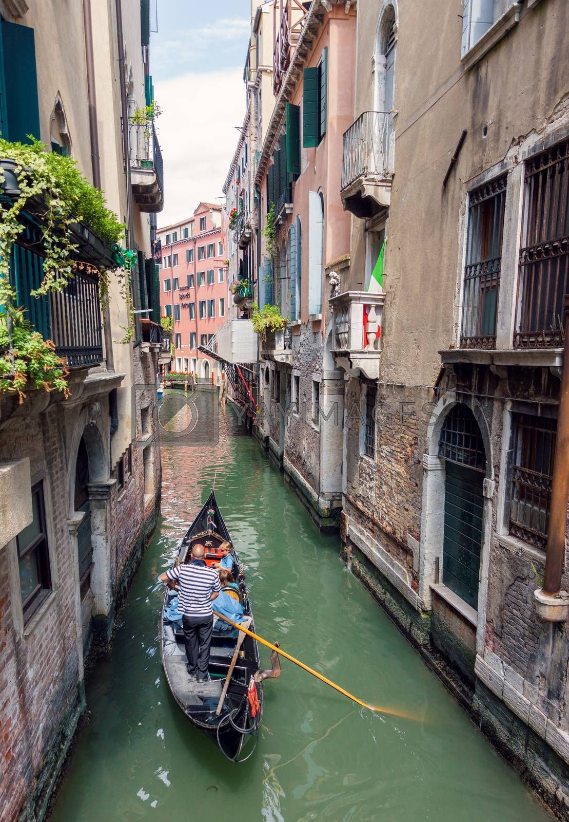 VENICE, ITALY - MAY 27, 2015: Traditional venetian gondola sailing tourists in remote canal, in Venice, Italy