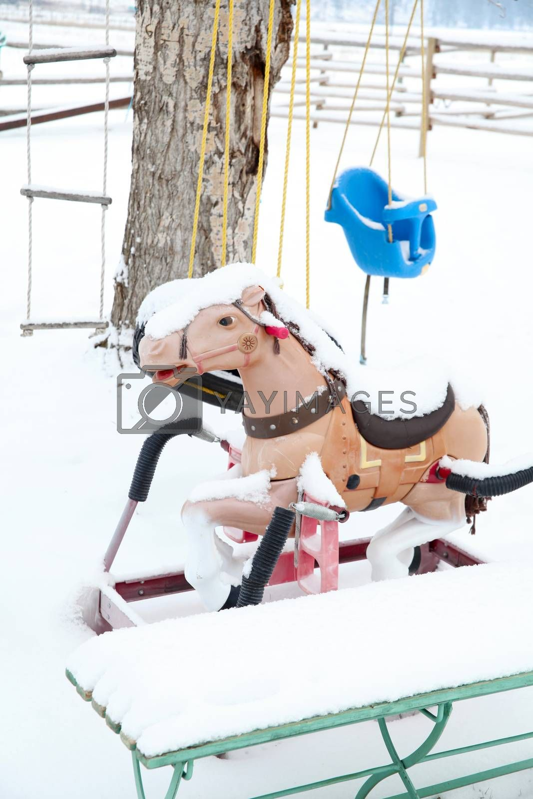 Snow covered outdoor swing, ladder and bouncy horse