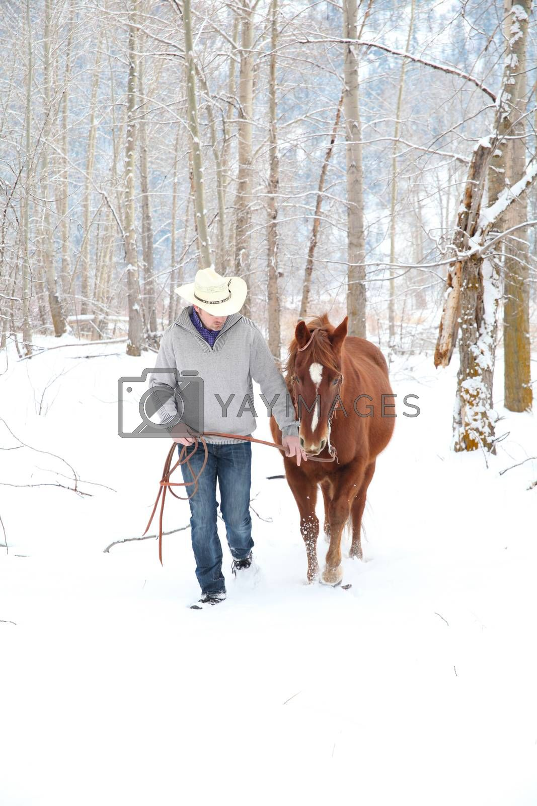 Young cowboy with his horse in a snow forest