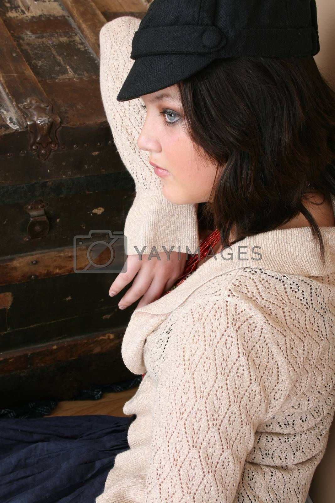Beautiful brunette teen sitting next to an antique trunk