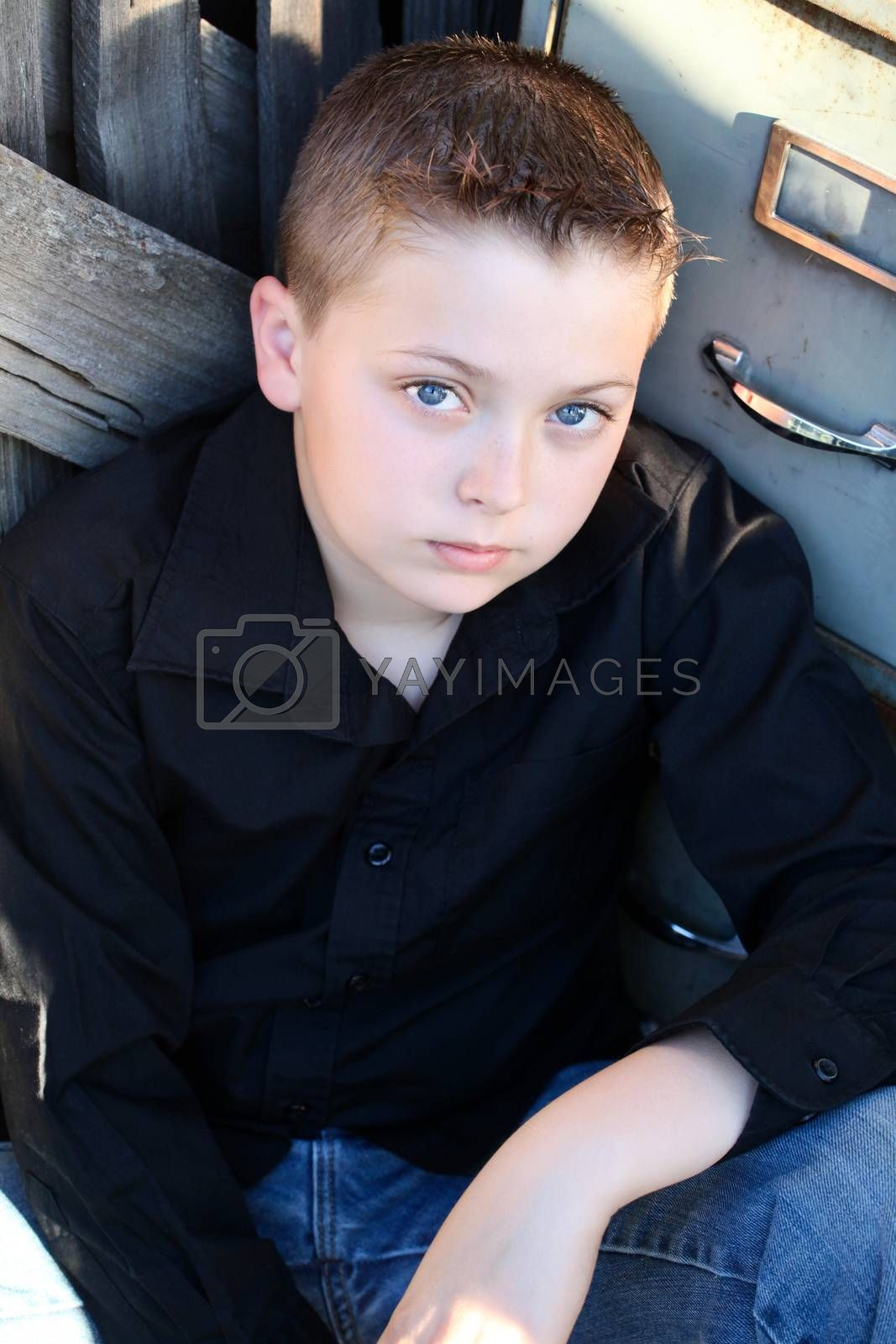 Young boy with deep blue eyes sitting against rustic background