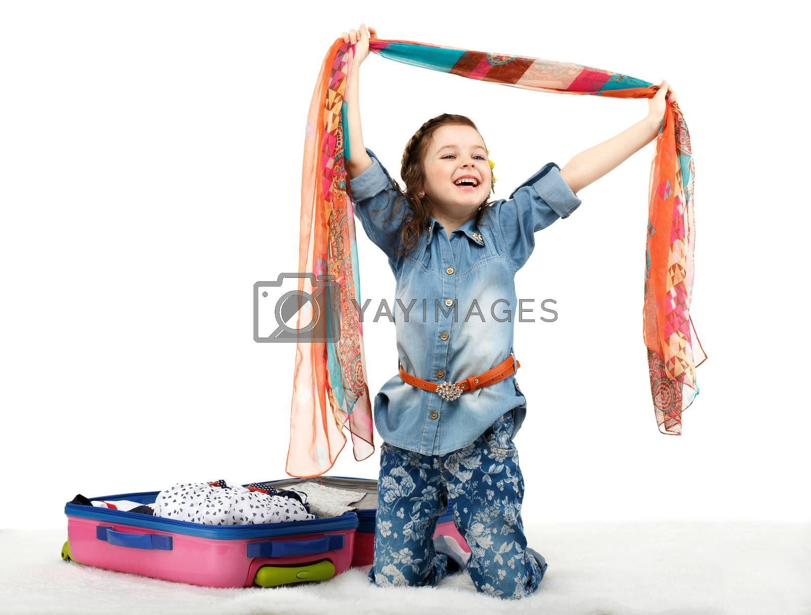 Fashionable little girl unpacking a suitcase isolated on white background