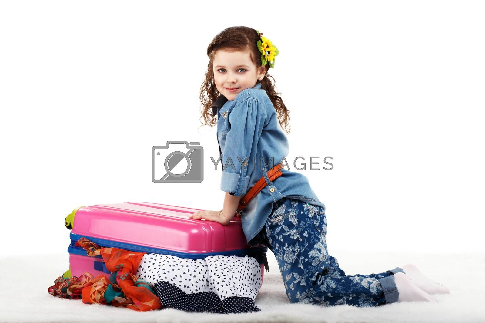 Fashionable little girl closes the suitcase with clothes isolated on white background