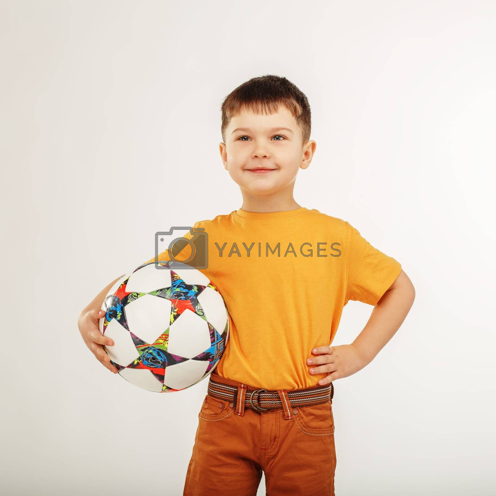 little smiling boy holding a soccer ball under his arm