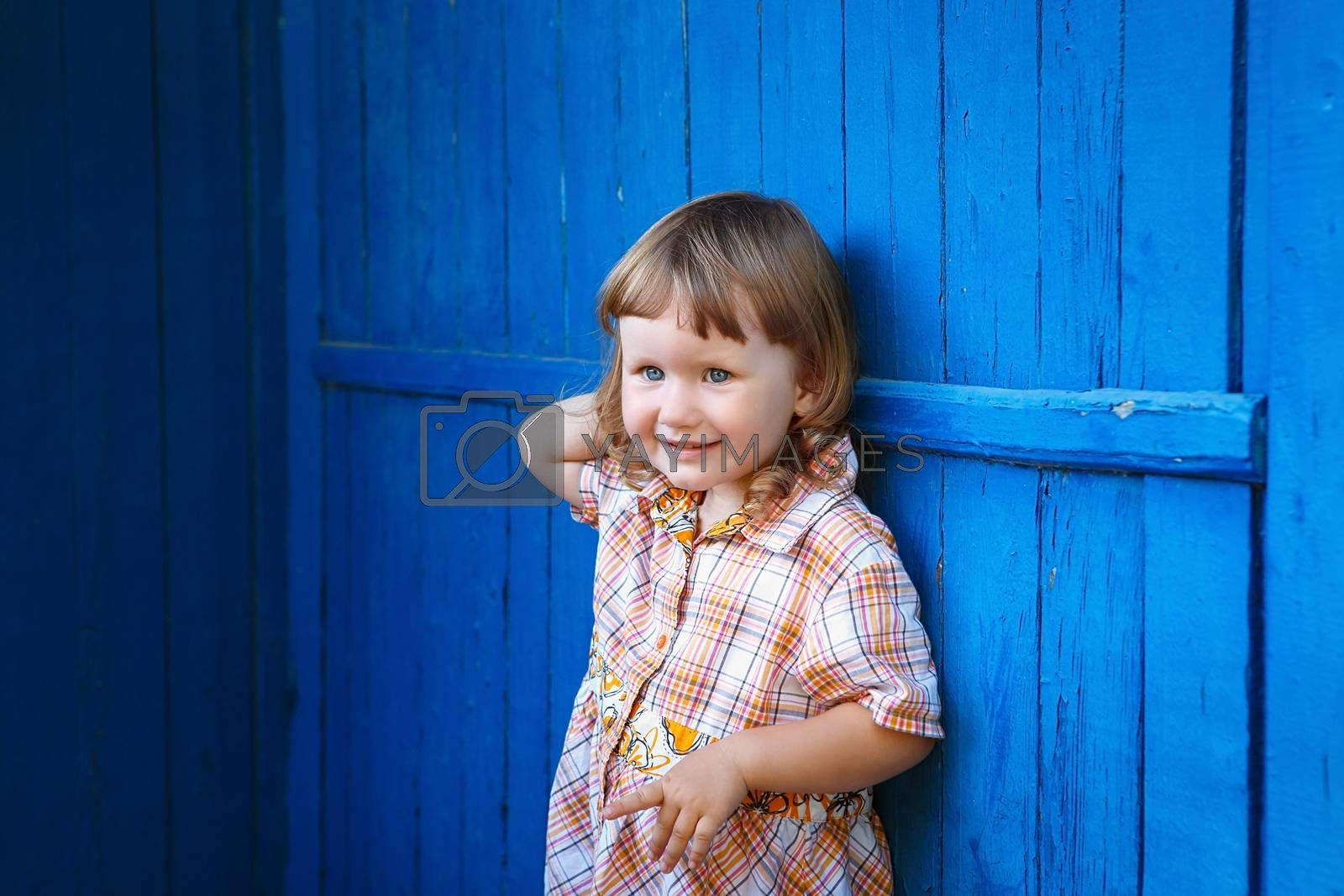 Portrait of happy joyful beautiful little girl against the old textured blue wall