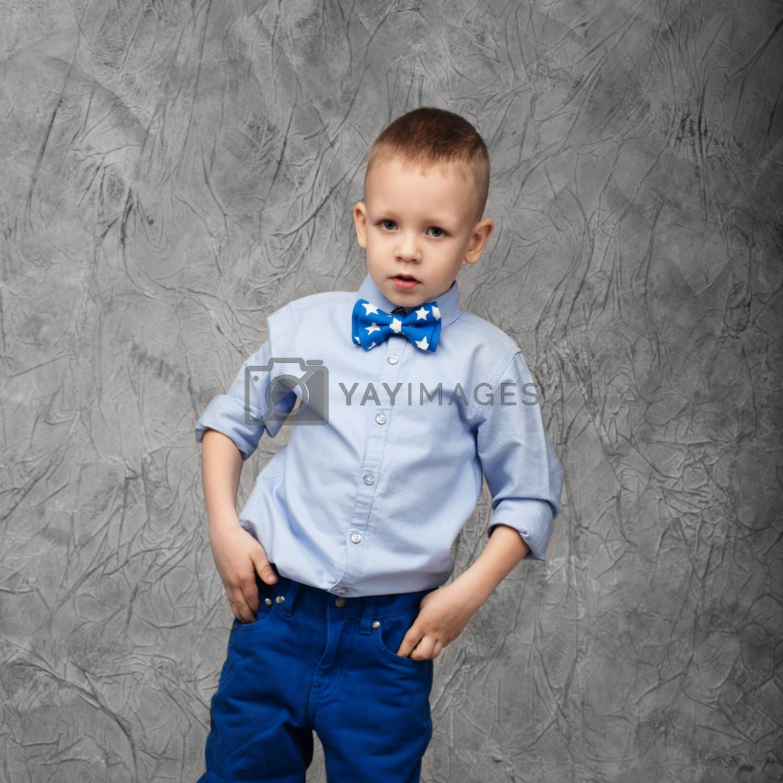 Portrait of a cute little boy in jeans, blue shirt and bow tie on a gray textural background in studio