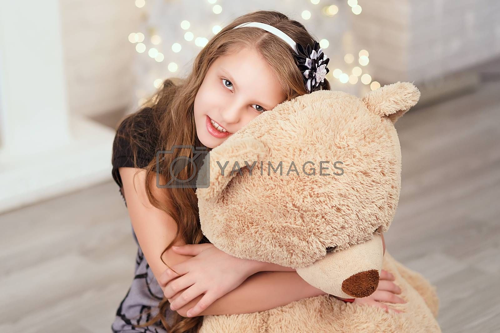 Young cute teenage girl hugs a big soft teddy bear in the interior with Christmas decorations