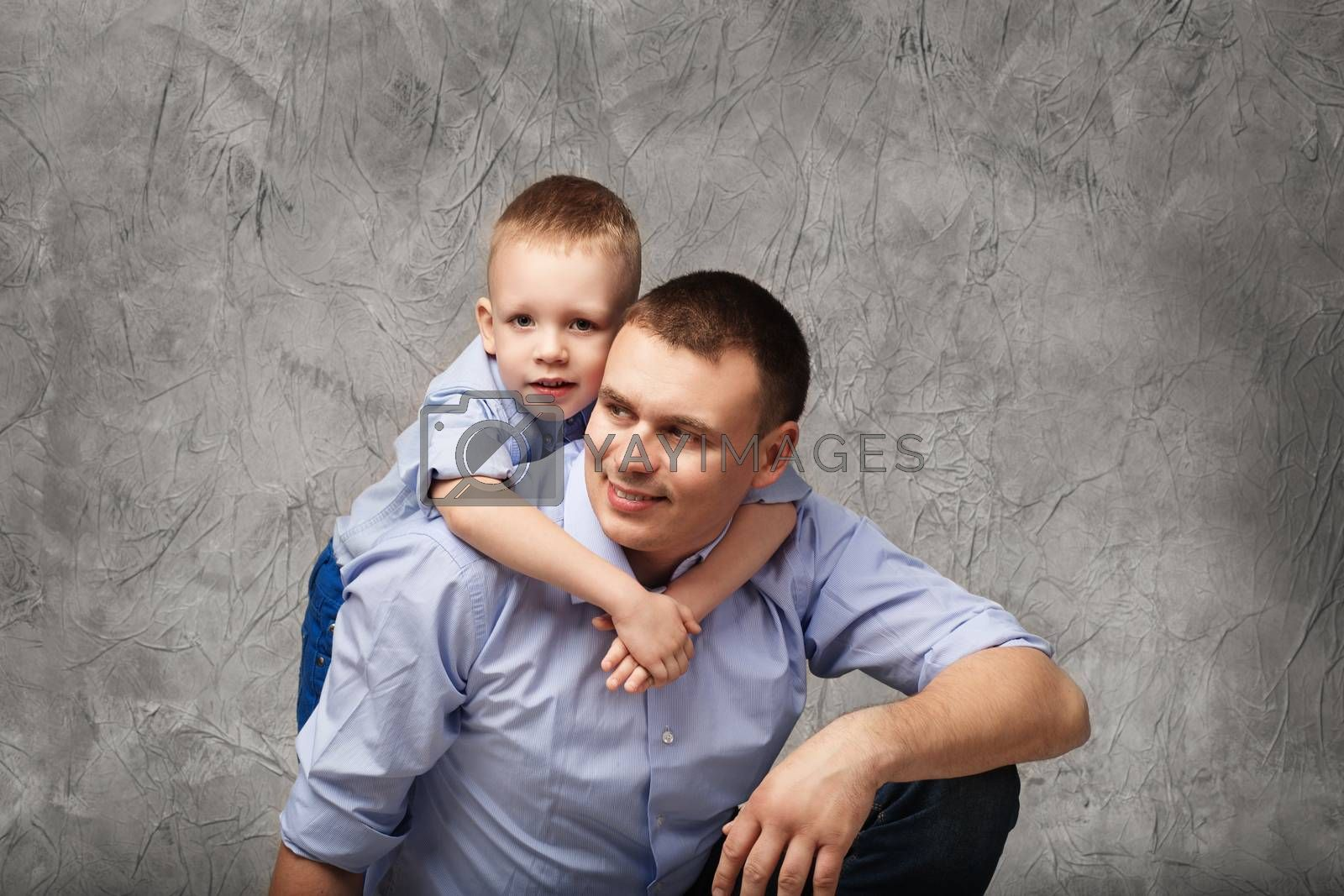 Father and little son in blue shirts in front of gray background by natazhekova