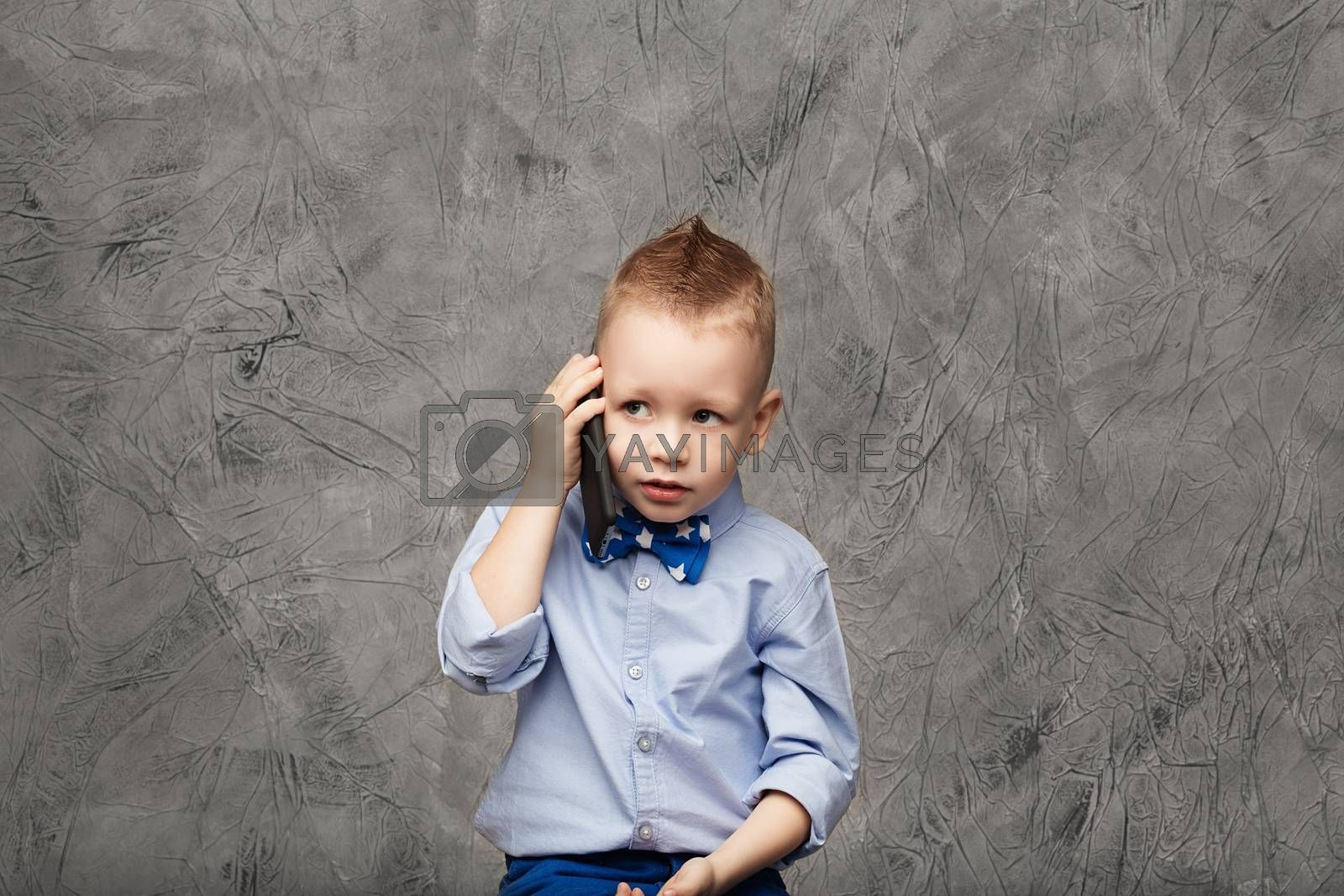 Portrait of a cute little boy in blue shirt and bow tie with mobile phone against gray textural background in studio. Business concept. Little boy businessman.