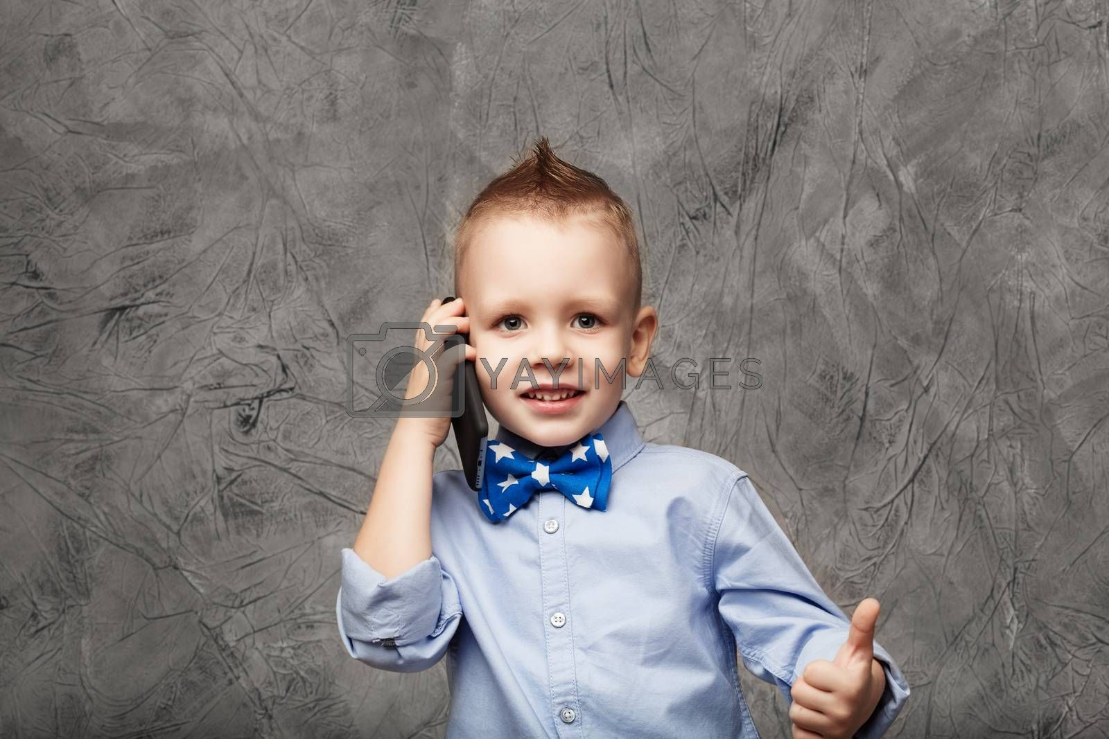 Portrait of a cute little boy in blue shirt and bow tie with mobile phone against gray textural background in studio. Kid shows thumb. Little boy American businessman.