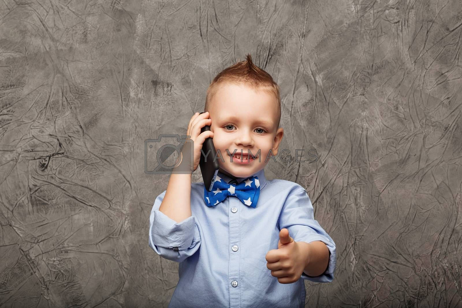 Portrait of a cute little boy in blue shirt and bow tie with mobile phone against gray textural background in studio. Kid shows thumb