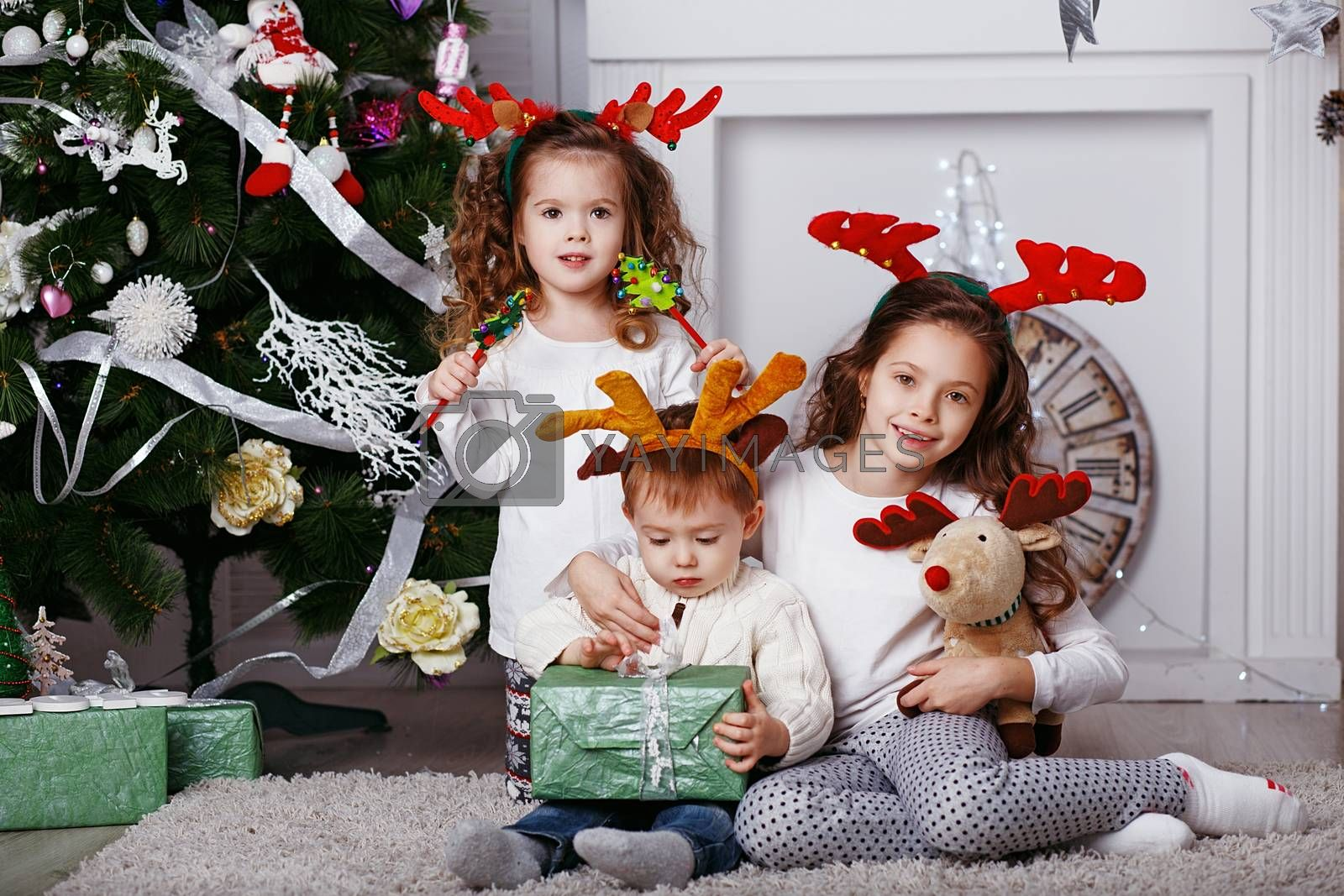 Little children in reindeer antlers In anticipation of new year and Christmas. Three little siblings opening christmas gifts. Kids in comfortable home clothes sitting on floor over Christmas tree