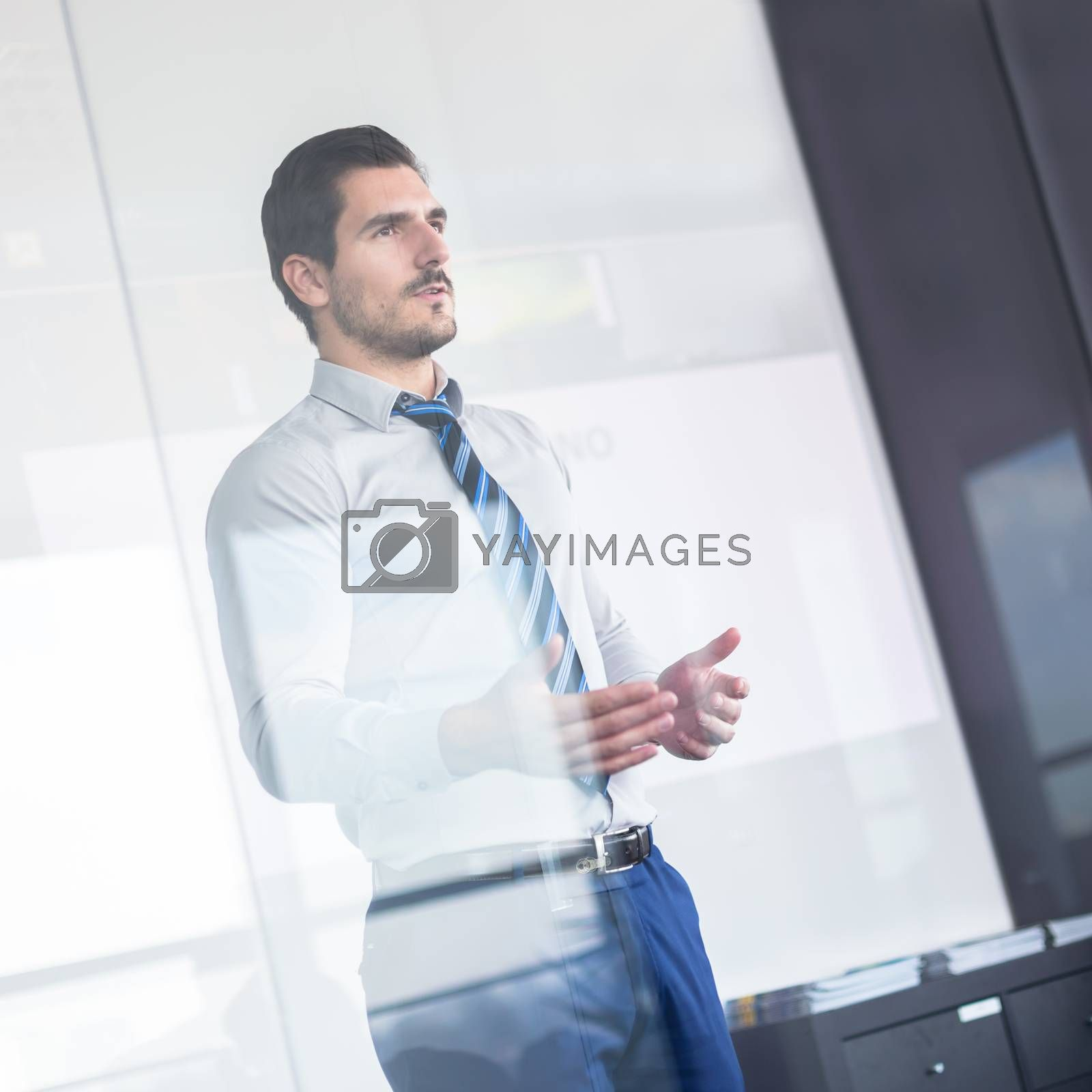Business man making a presentation in front of whiteboard. View through glass.