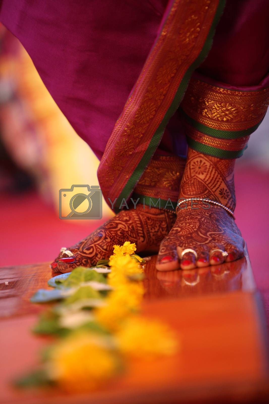 The feet of a bride during a traditional Indian wedding ritual of stepping over flowers.