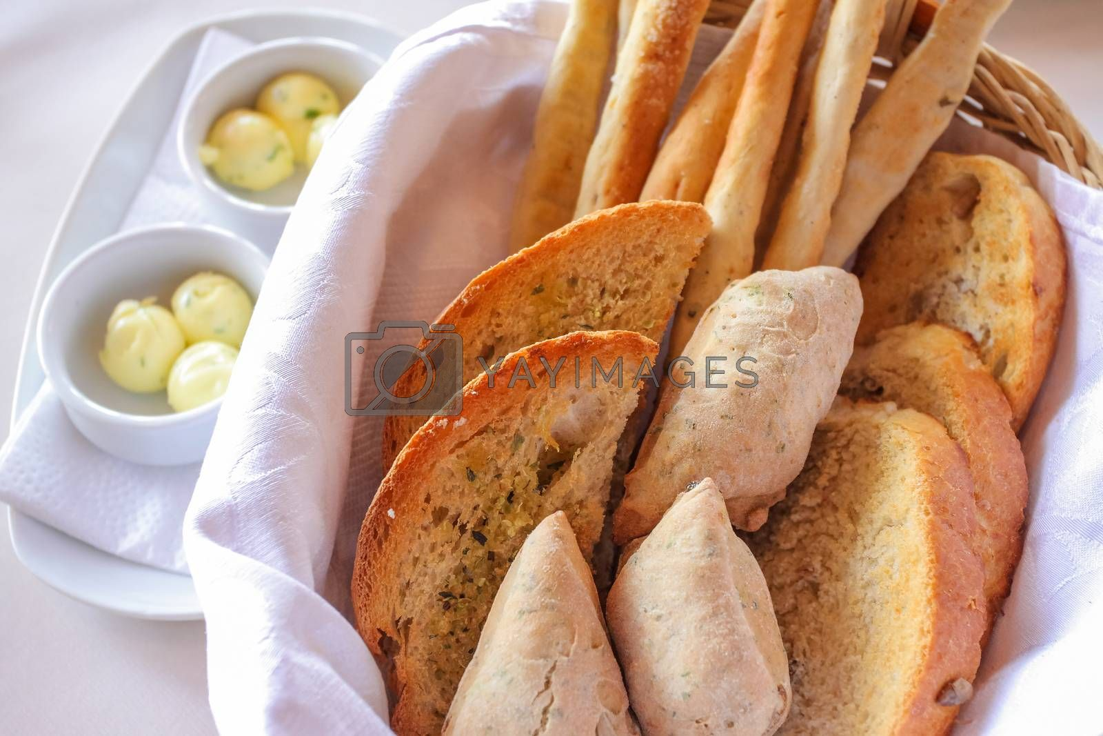 freshly backed various bread, tost, bagettes, served in a basket with white napkin.