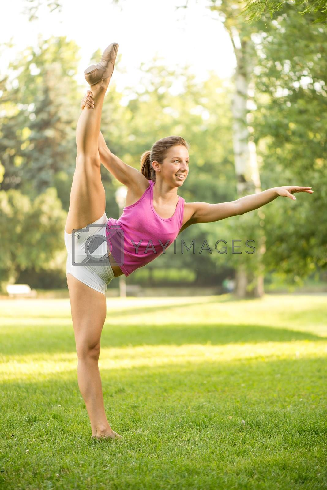 Cute girl doing stretching exercises in the park, standing on one leg.