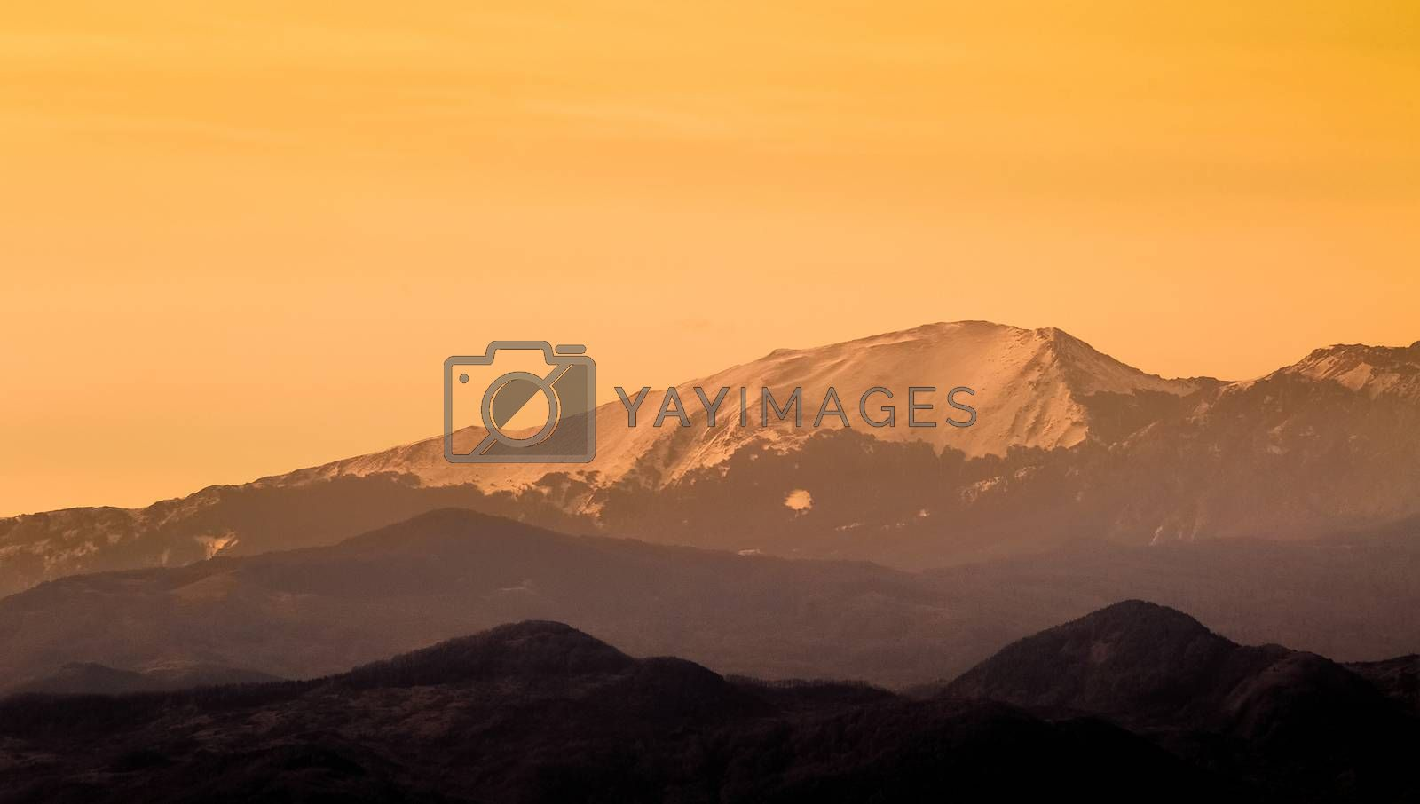 mountains at sunset with snow, natural light tint warm