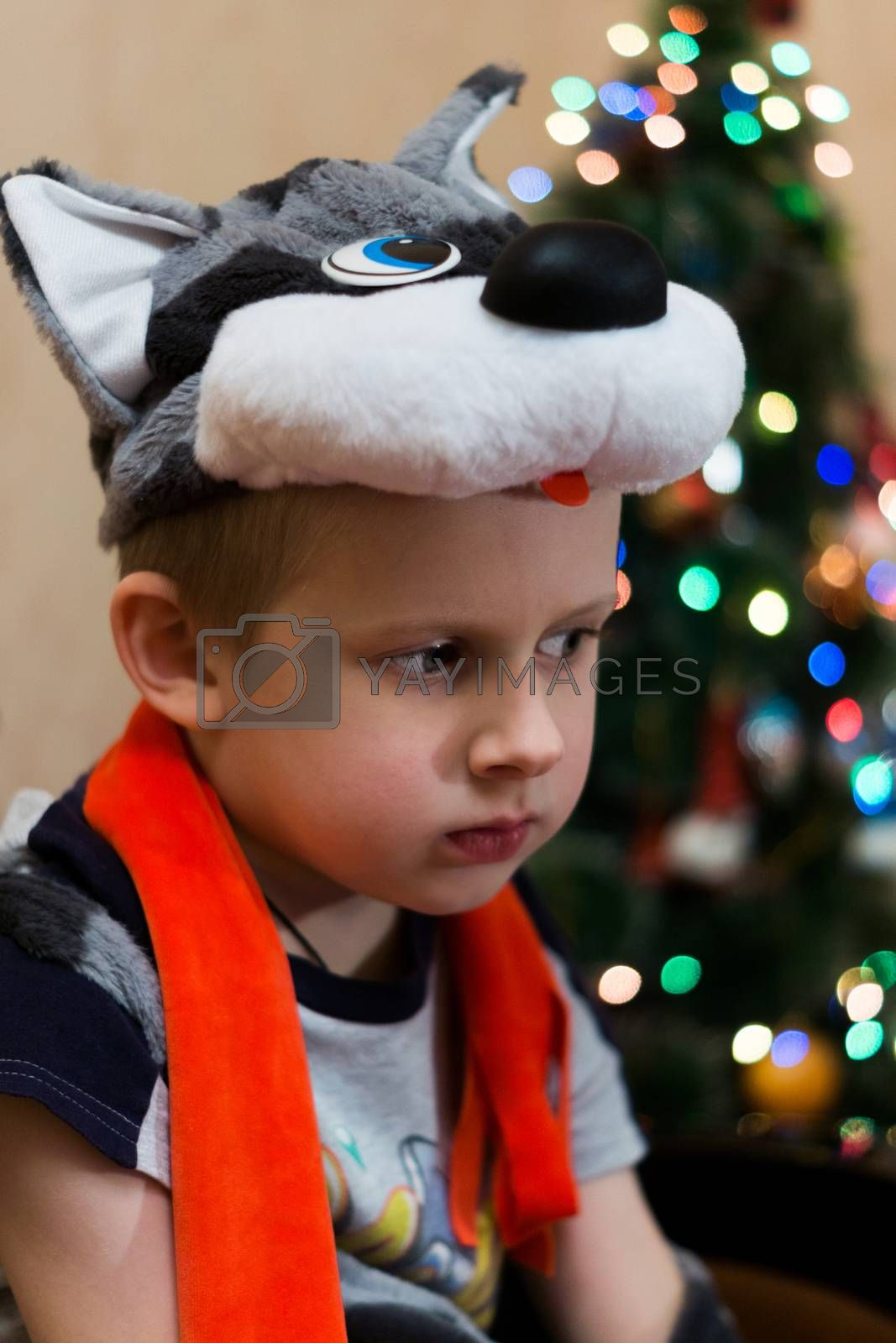 The photo depicts a sad boy at the tree
