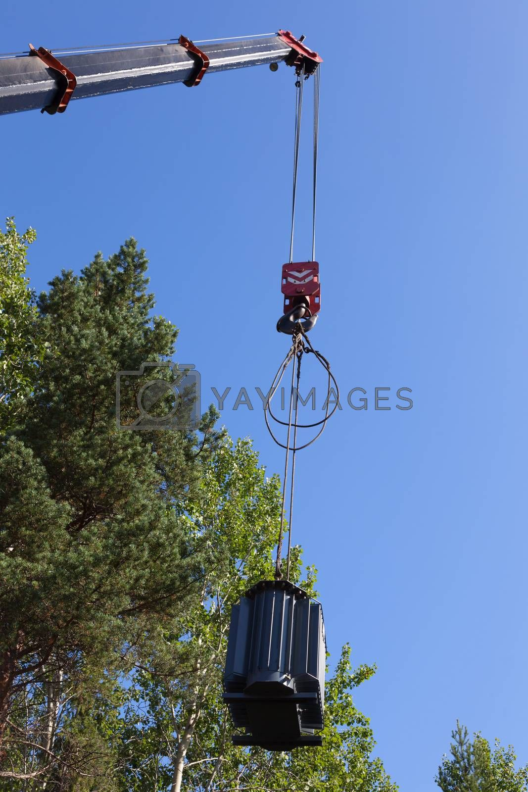 Crane hook lifts up the power transformer against the green forest