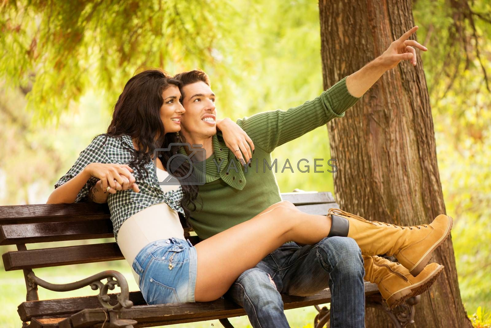 Attractive young heterosexual couple sitting on a park bench. Attractive girl sitting on the bench, and her long pretty legs holding on knees her boyfriend, who outstretched finger pointing at something.