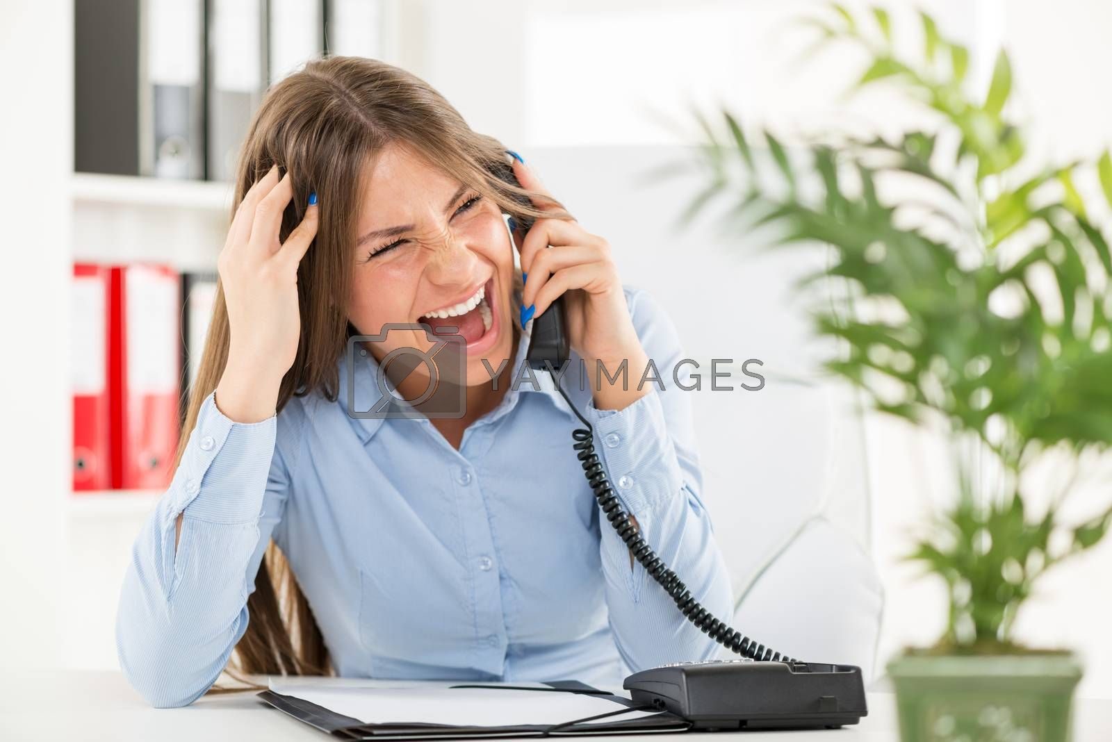 Young businesswoman in her office, sitting at an office desk and with an expression of anger on her face screaming in the phone.