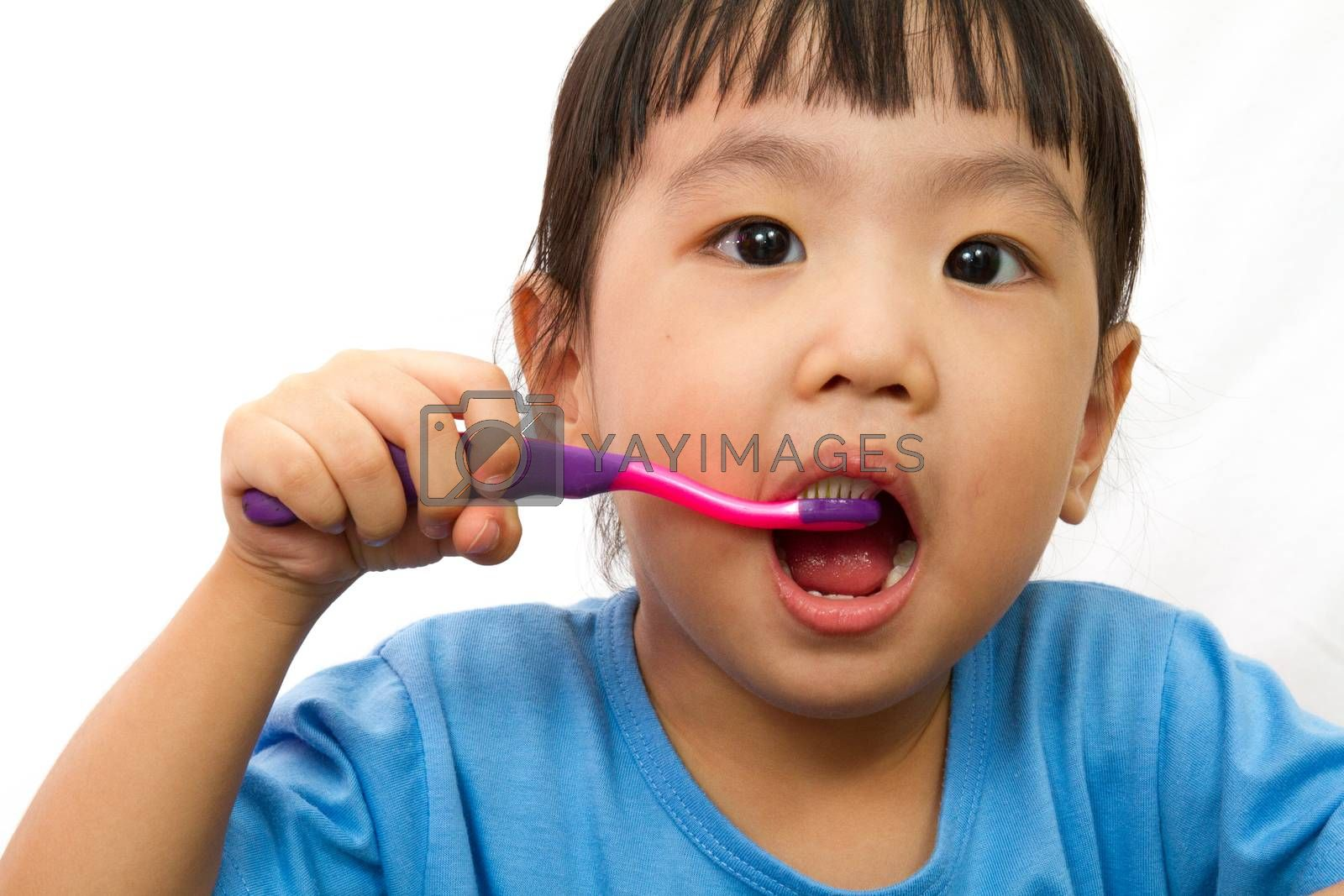 Chinese little girl brushing teeth in plain white isolated background.