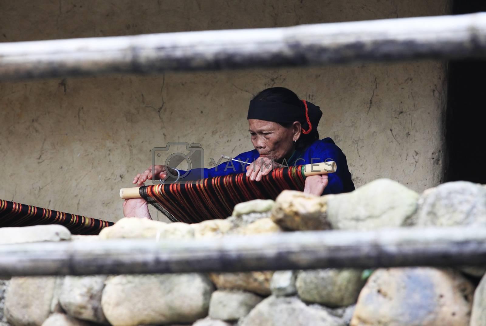 Hainan, China - April 7, 2012: Mature woman works on an ancient loom in Hainan. China