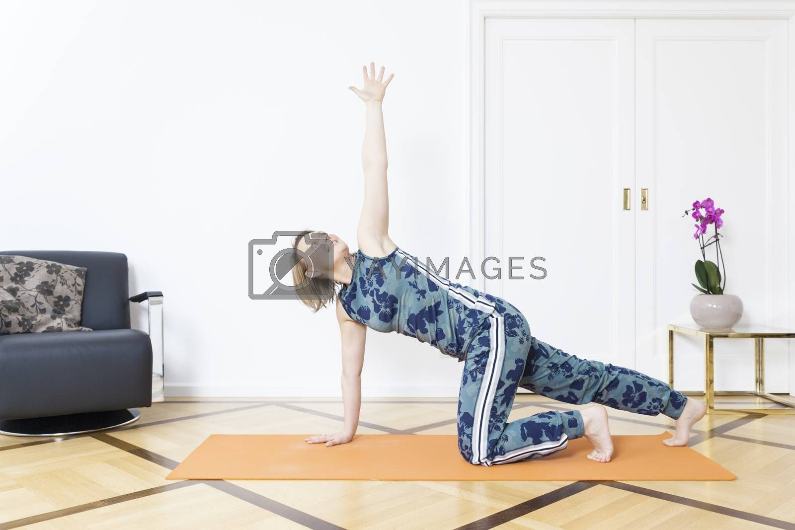 A woman doing yoga at home by magann