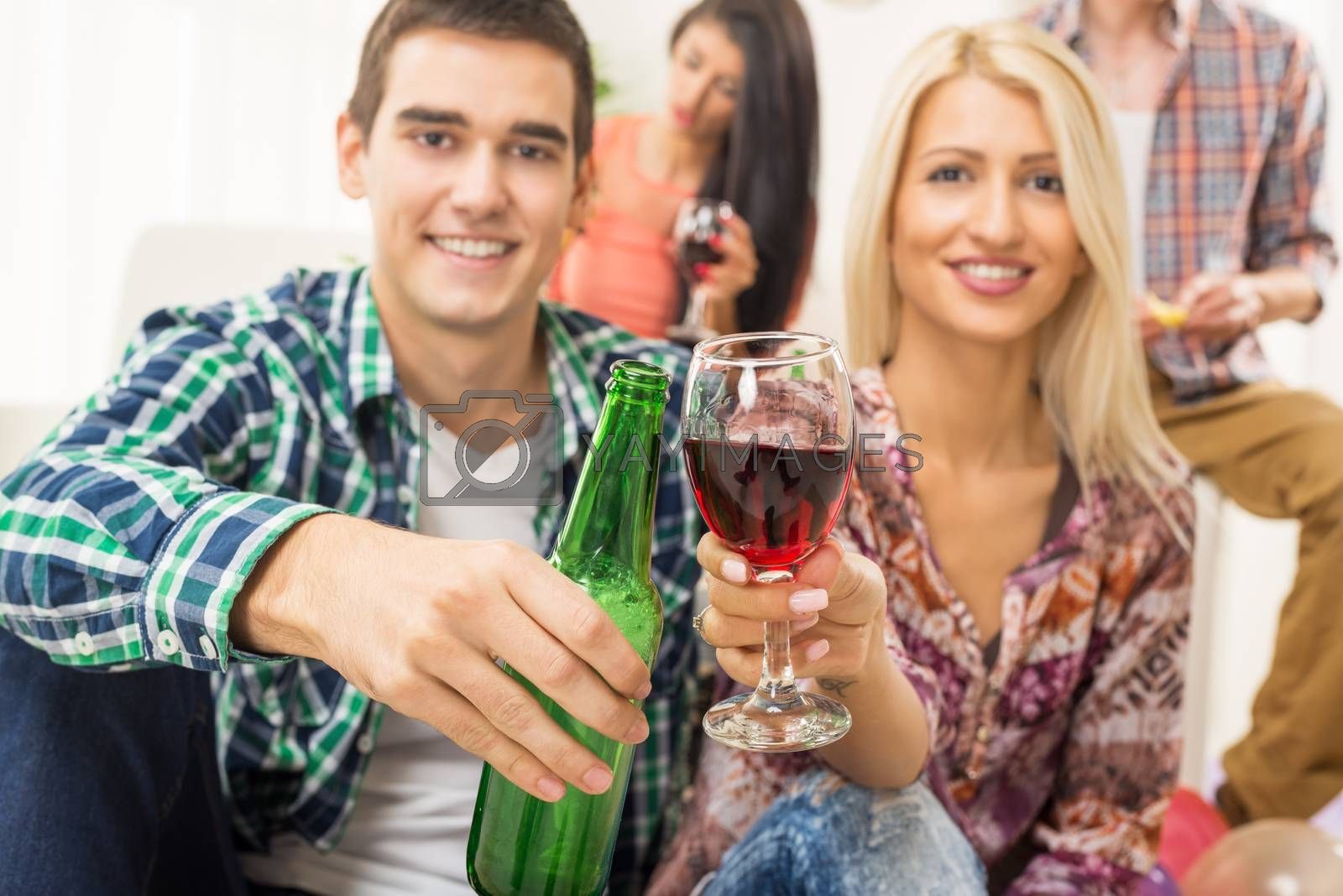 Young couple at home party with a smile on their faces out of focus, toasting with drinks that are in the foreground. In the background is another young couple.