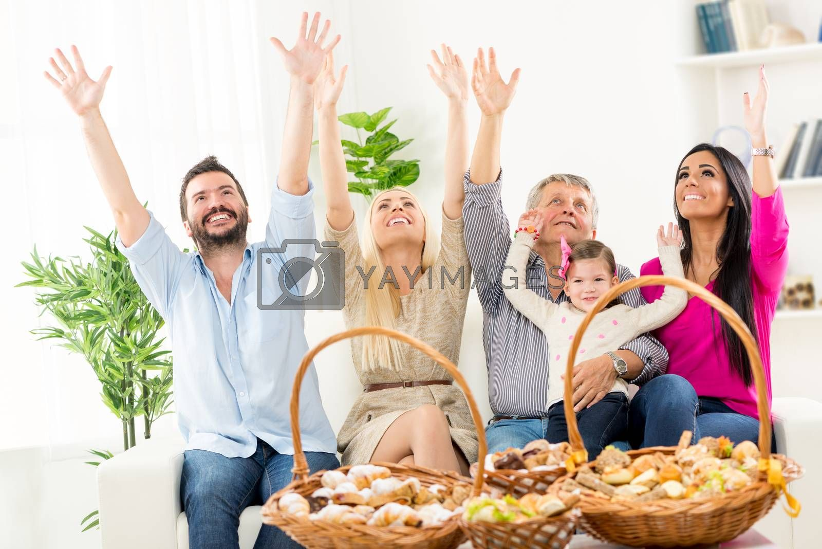 Happy family sitting on couch with arms raised, looking up. In front of them on the table are woven baskets decorated with beautiful pastries.