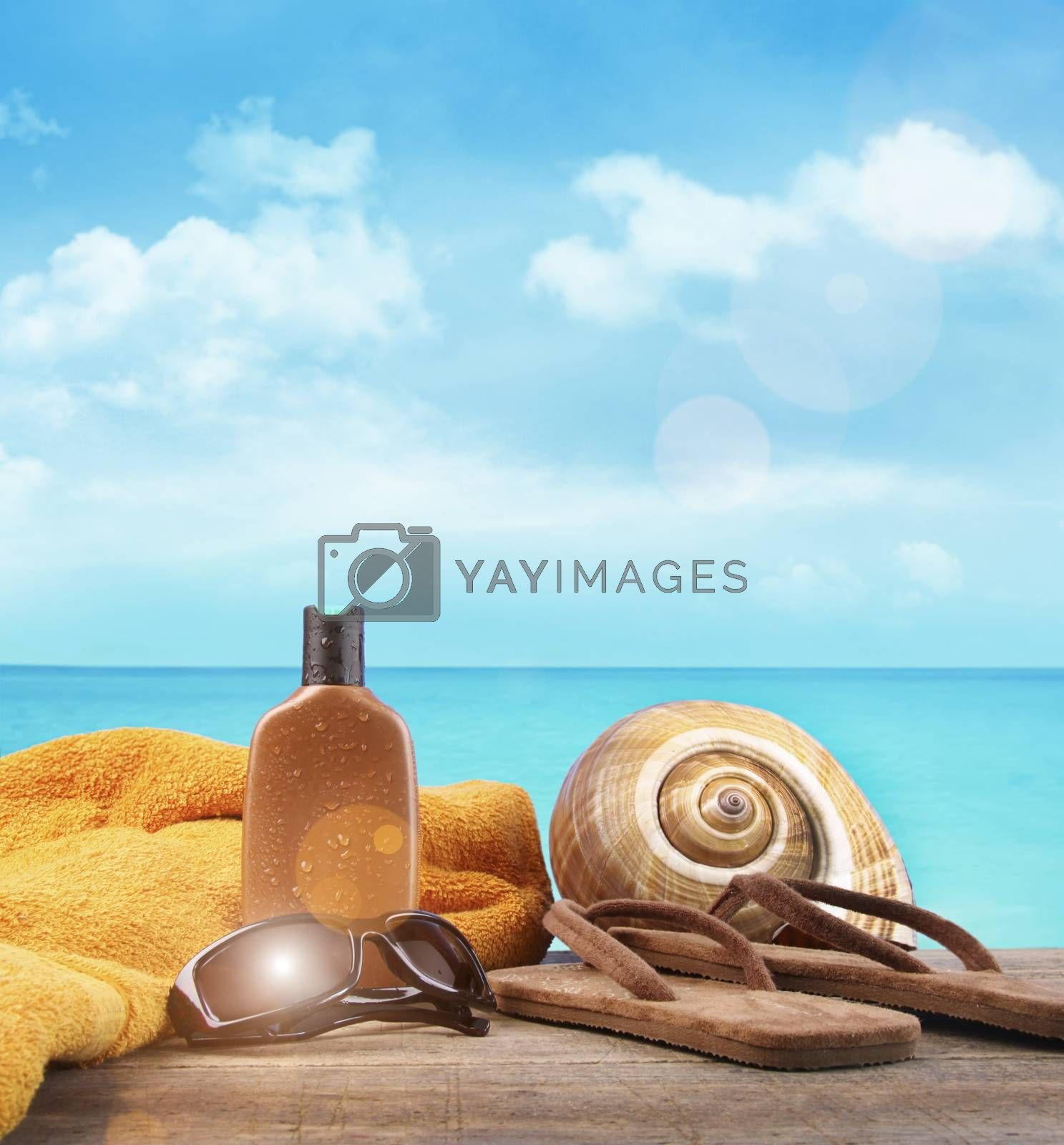 Suntan lotion with towel and sandals at the beach