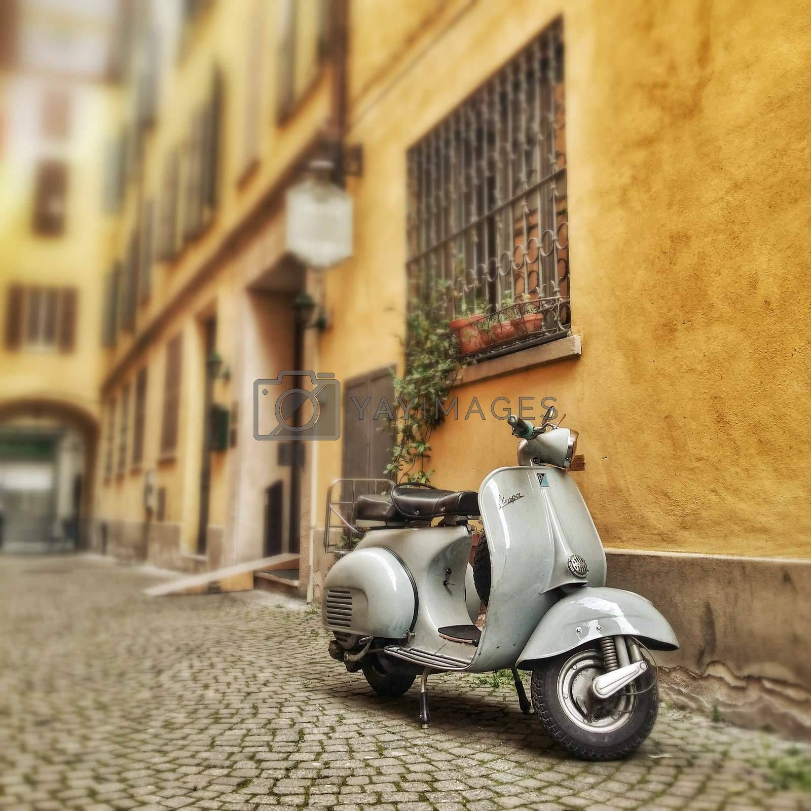 a 60's vespa motorcycle in a typical italian old town alley.
