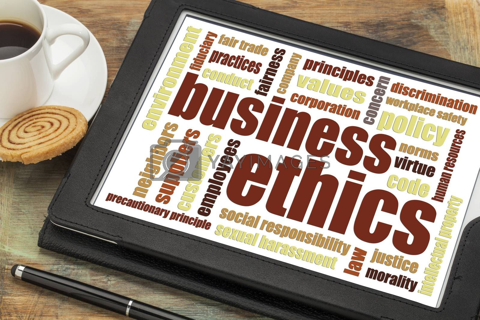 business ethics word cloud on a digital tablet with cup of coffee
