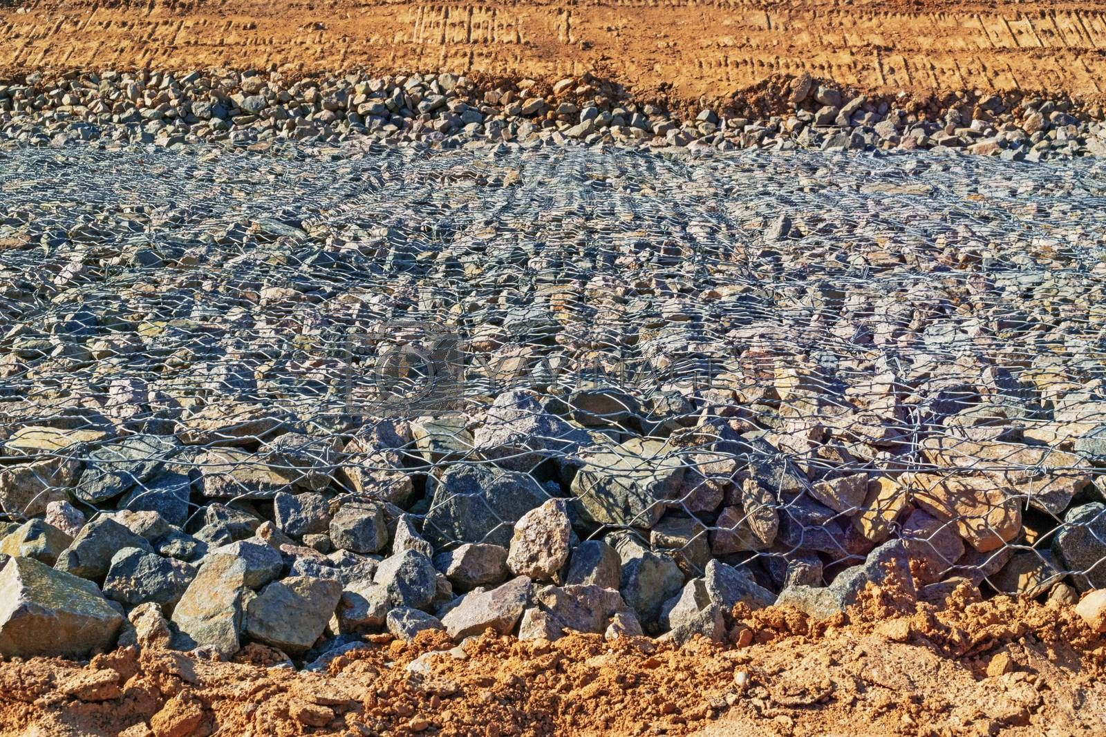 Preparation of the river bank near village for protection against a flood.Construction of the dam - granite boulders piled in metall grid on the surface of the dam.