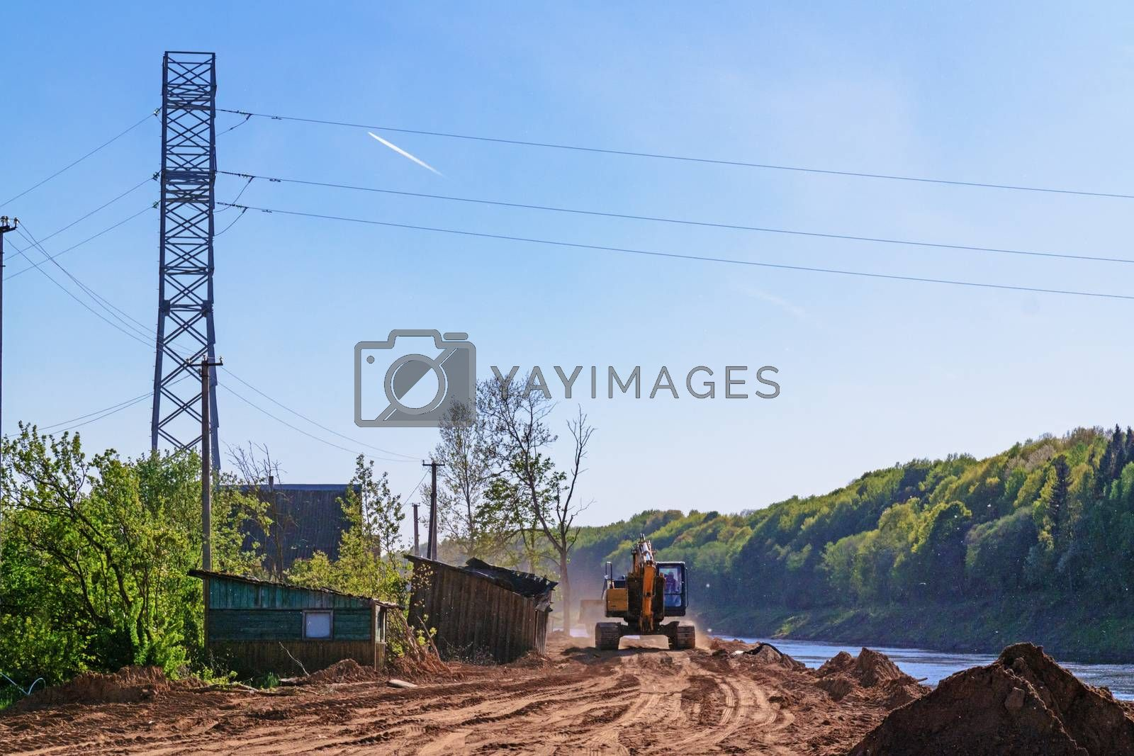 Preparation of the river bank near village for protection against a flood.