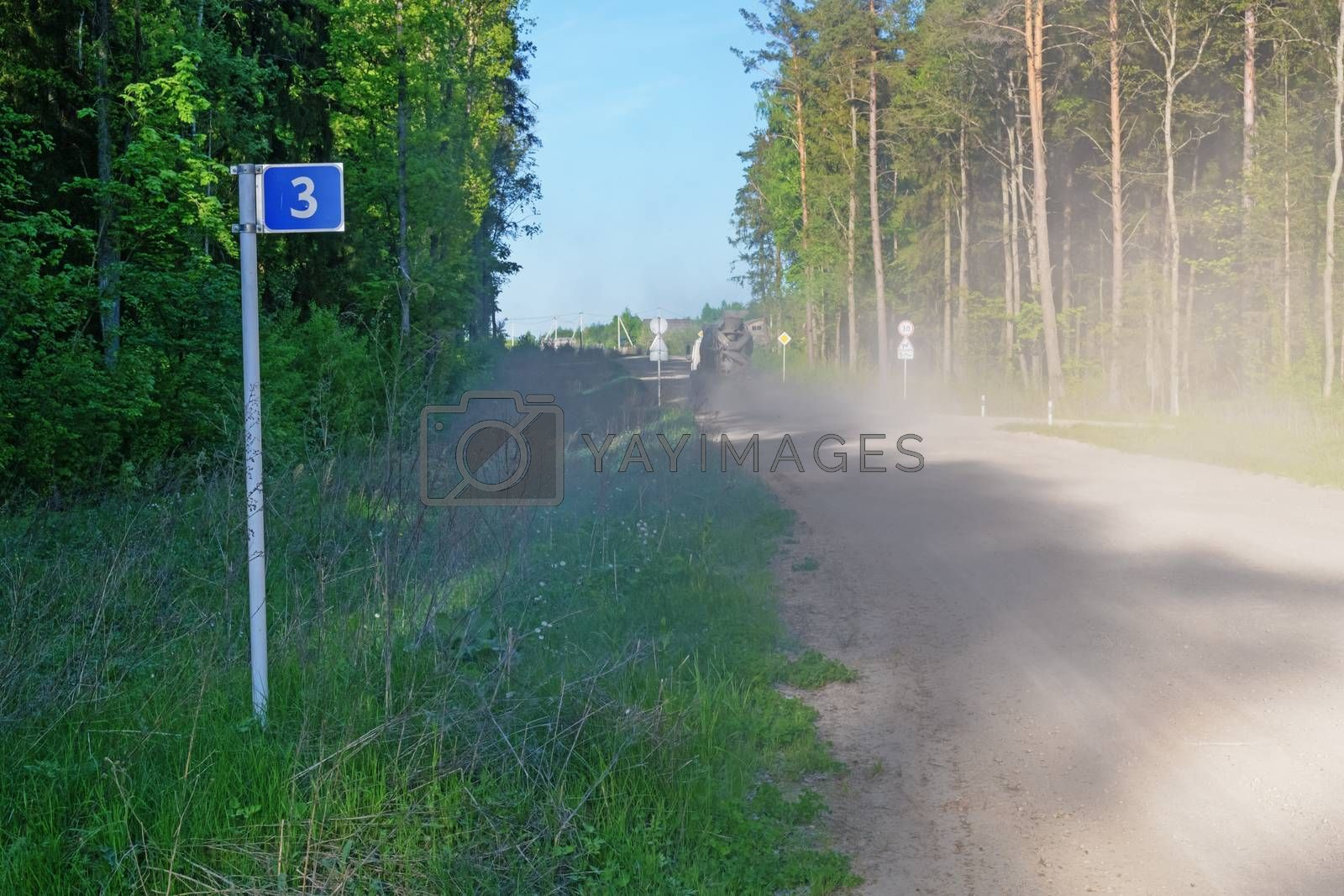 Left photo road sign - 3 kilometers. Over the road a cloud of dust from the traveling vehicle.